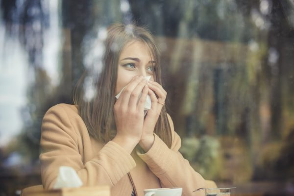 Women Struggling with Allergies Looking Through a Window