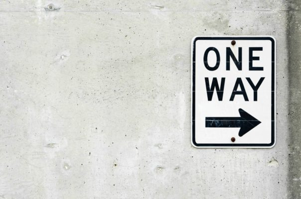 One Way Street Sign on a Concrete Wall