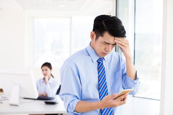 Man experiencing digital eye strain and a headache from using a smartphone
